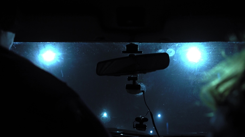 The driver rides at night on a lighted road. The car cracks and staggers. Inside view. Dashboard, radio, DVR. Overtaking. Oncoming cars blind eyes. Headlights light the way. Road signs and marking.
