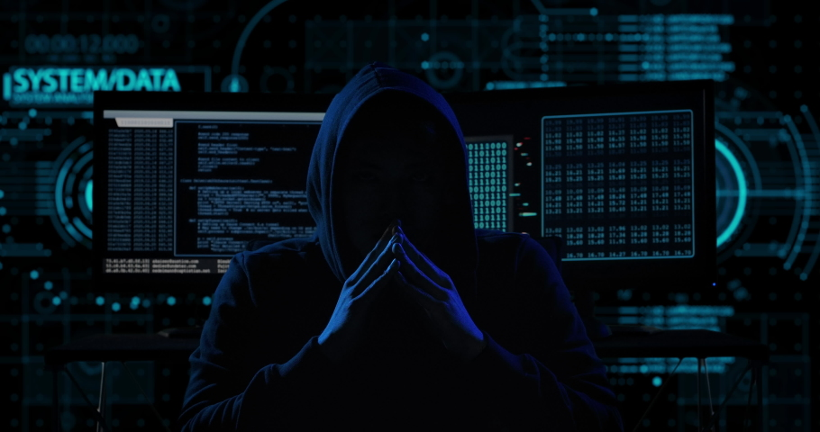 Portrait of mysterious hooded hacker sitting at desk and looking at the camera after breaks into government data servers in dark atmosphere with system codes animation in background. Royalty-Free Stock Footage #1045464274