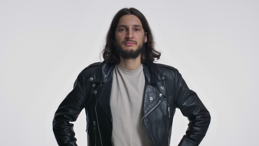 An attractive young man with long hair in a black leather jacket is nodding his head positively isolated over white background