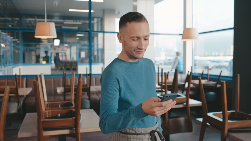 Portrait of happy cafe owner standing in apron and using smartphone making online food supply order on empty cafe background. Small business, communication, people and service concept