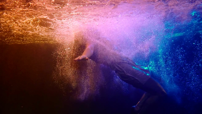underwater shot in swimming pool, woman is falling inside water, plunging and diving Royalty-Free Stock Footage #1045493158