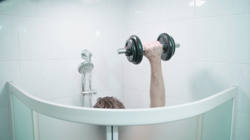 Bodybuilding while taking a shower 4K. Medium shot above the shower cabin with person arm in focus while lifting weights. | Shutterstock HD Video #1045502809