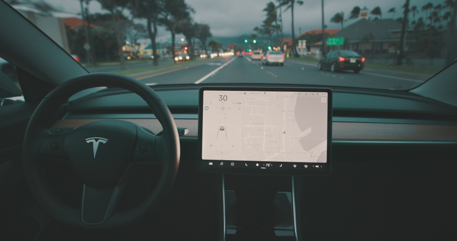MAUI, HAWAII - January 19, 2020: A Tesla Model 3 driving with the latest self driving software update in town traffic, the future of self driving vehicles is here