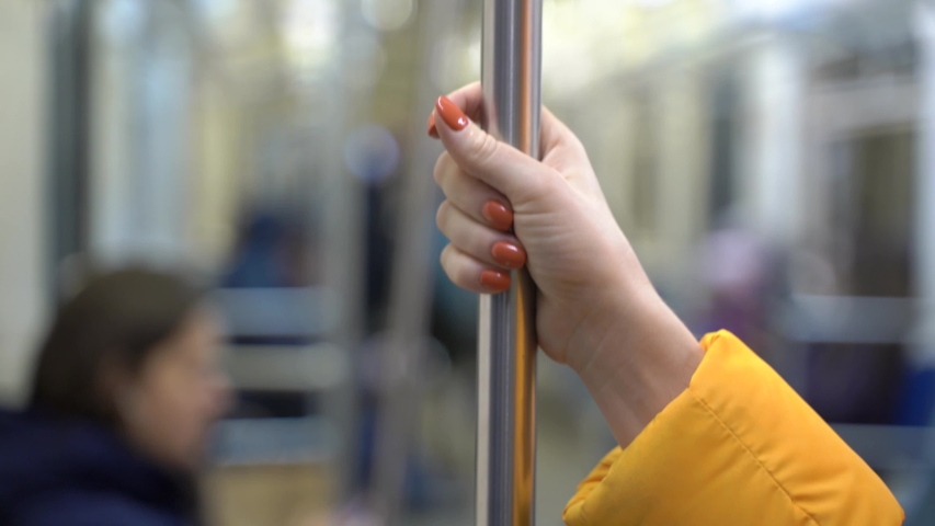 A female hand is taken by a handrail in public transport. The girl holds the handle in the subway car. The concept of germs and disease infection in public places. Royalty-Free Stock Footage #1045512340