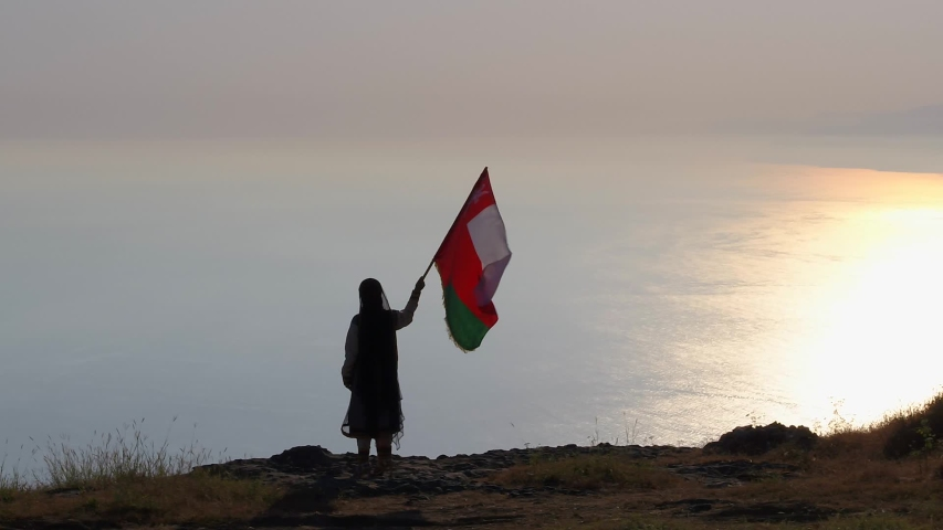 Aerial shot of a young Omani girl holds the flag of the Sultanate of Oman over the top of the mountain during sunset in the south of Sultanate of Oman .