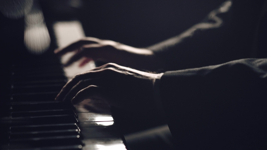 Man two hands plays gentle classical music on a grand piano. Professional pianist