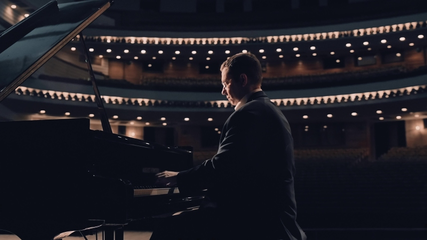 Handsome middle-aged pianist playing on a grand piano on big stage in concert hall with dimmed light    Shutterstock HD Video #1045514422