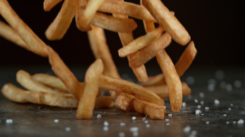 Super Slow Motion Shot of Falling Fresh French Fries on Black Table at 1000fps.