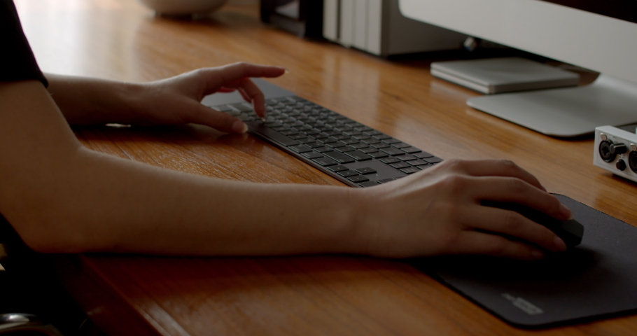 Close up of female video editor's hands as she clicks keyboard and navigates a computer program with her mouse working on an edit for a tight deadline and client in her home office | Shutterstock HD Video #1045518973