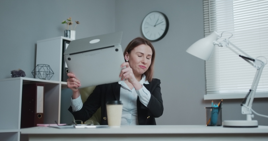Business woman reading bad news on laptop computer at coworking space. Upset woman closing down laptop in office. Tired woman breathing deep at workplace. Business woman doing yoga exercise | Shutterstock HD Video #1045526812