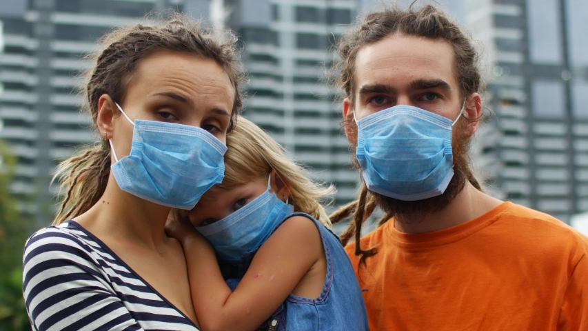 Family in protective medical masks against the background of the metropolis, coronavirus epidemic 2019-nCoV