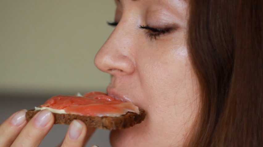Closeup woman who eating a sandwich with red fish and butter. Girl mouth bites a salmon sandwich from whole wheat bread. | Shutterstock HD Video #1045530907