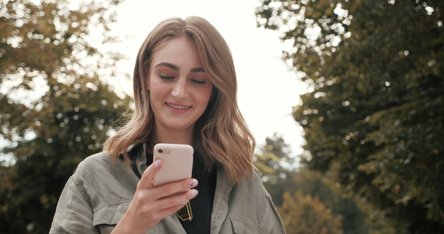 Young Attractive Woman Standing in the Town with Mobile phone and typing Messages on it. Looking stylish and nice. Having Beautiful Makeup and chic hair. Good looking Girl with Smartphone. | Shutterstock HD Video #1045546618