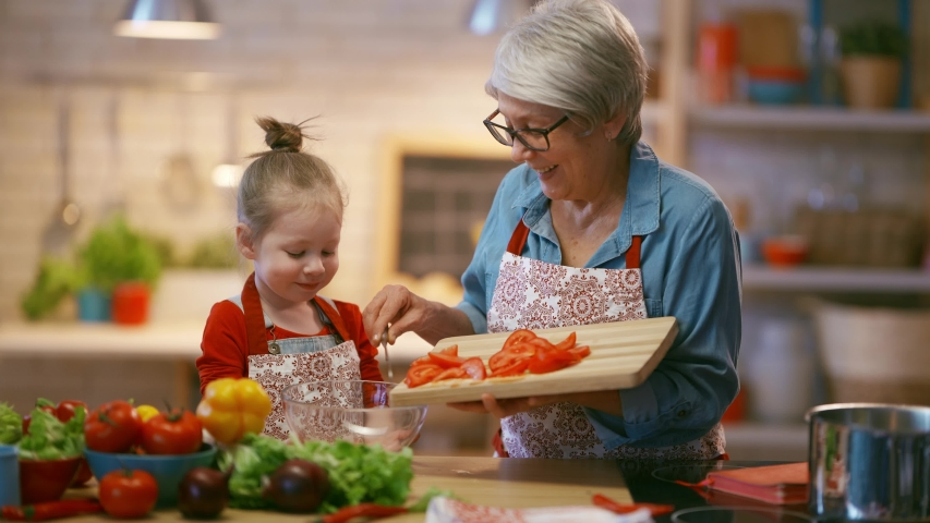 Healthy food at home. Happy family in the kitchen. Grandma and child are preparing the vegetables.  Royalty-Free Stock Footage #1045550434