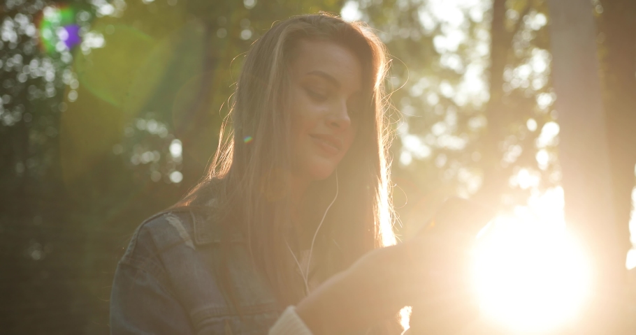 Attractive girl listens to music in the park Extremely beautiful sunset and sunshine