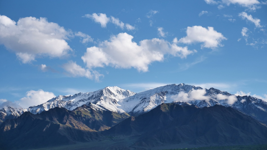 Time lapse of clouds and snow clad Himalayan mountains while blue sky in the background. Shadow of clouds creating patterns on the mighty barren mountains near Leh, Ladakh