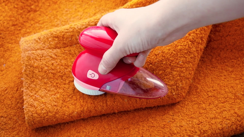Clothes care. Lint shaver or fabric shaver or fuzz remover in female hand. Woman removing lint on orange wool coat with handheld electric defuzzer | Shutterstock HD Video #1045563775