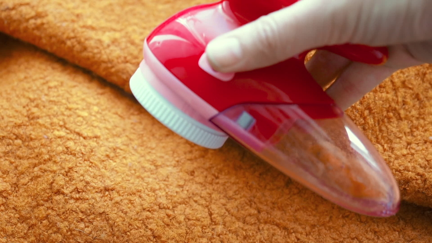 Clothes care. Lint shaver or fabric shaver or fuzz remover in female hand. Woman removing lint on orange wool coat with handheld electric defuzzer | Shutterstock HD Video #1045563778