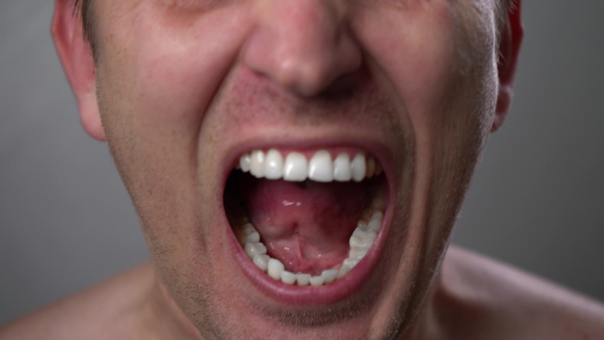 Man with angry facial expression is screaming out loud. Furious man due to financial crisis. Scream, anger, hopelessness. Furious yelling man. Anger emotions. Anger. Violence. Mouth and grin close-up. | Shutterstock HD Video #1045577689