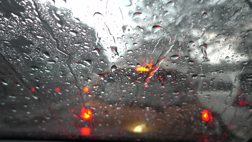Rain falling on car windshield view. Drive car on traffic jam street at heavy rain storm, inside a car driving,blurred traffic light background.
