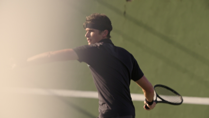 Professional tennis player hitting forehands strokes on hard court. Fit young man in sportswear playing tennis on hard court on a sunny day.