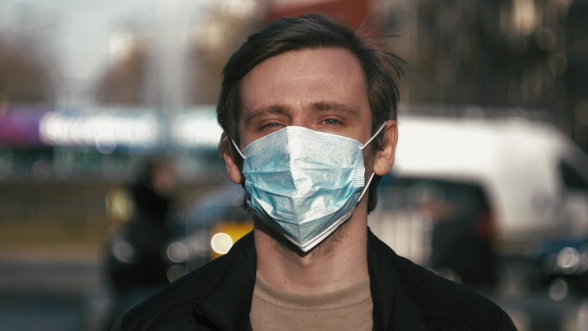 Pandemic, portrait of a young tourist man wearing protective mask on street crowd people. the concept health and safety, N1H1 coronavirus quarantine, virus protection | Shutterstock HD Video #1045586917