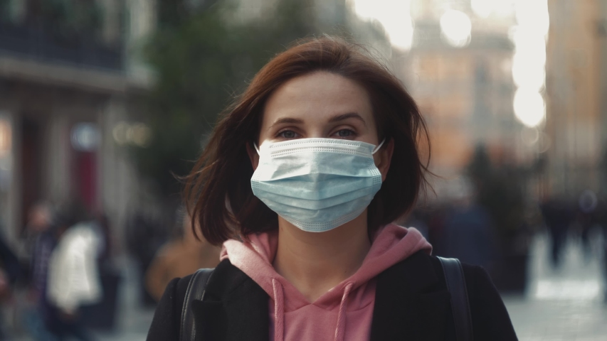 Pandemic, portrait of a young tourist woman wearing protective mask on street crowd people. covid concept health and safety, N1H1 coronavirus quarantine, virus protection #1045586953