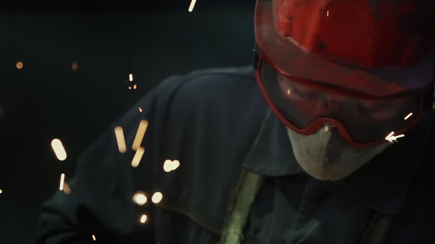 Welding Workshop in factory, welder in protective mask, glasses and red helmet makes manual work, Heavy Machinery, Bokeh Sparks, Close Up, Slow Motion, Cinematic | Shutterstock HD Video #1045613620