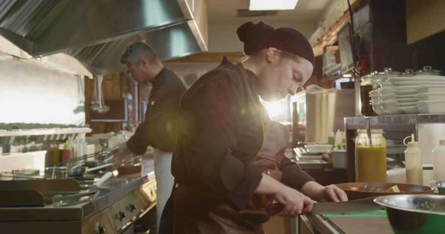 Side view of a Caucasian female cook working in a busy restaurant kitchen, slicing vegetables, her colleagues working in the background