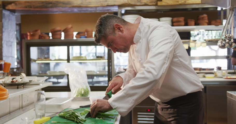 Side view of a Caucasian male chef working in a busy restaurant kitchen, slicing spring onions, female cook walking in the background