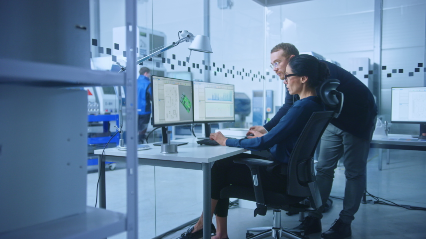 Modern Electronics Factory: Male Supervisor Talks to a Female Electrical Engineer who Works on Computer with CAD Software. Developing PCB, Microchips, Semiconductors and Telecommunications Equipment Royalty-Free Stock Footage #1045628581