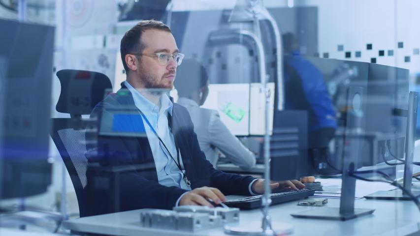 Factory Office: Industrial Engineer working on Personal Computer, On his Desk Lying Various Blueprints, Electronic Mechanismnents, Heavy Industry Machinery Parts. Design, Development and Manufacturing Royalty-Free Stock Footage #1045628599