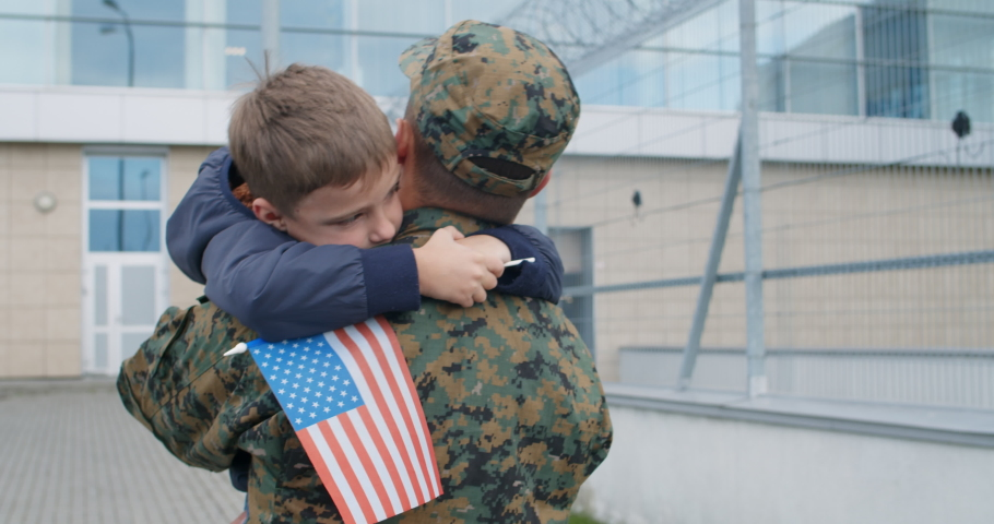 Back view of soldier walking and holding his son in arms. Kid with american flag putting his arms around neck of his military father and being in his arms. Patriot coming back home