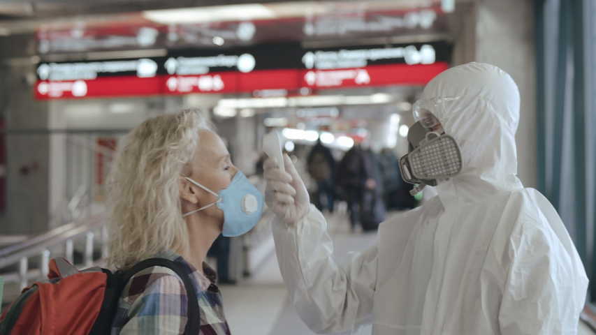 Controlling people's temperature and health at the entrance to airport, railway station or hypermarket. Medical worker in a protective suit screening passenger to check the Covid-19 symptoms