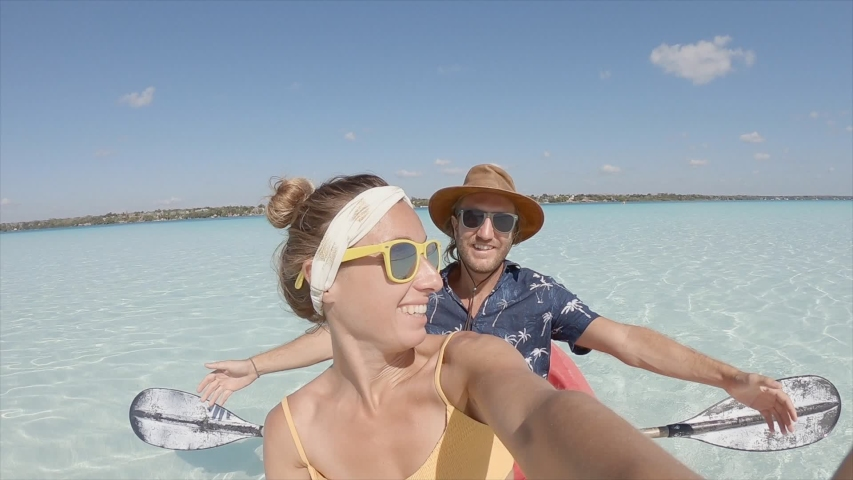 Happy young couple on canoe in Mexico taking selfie portrait and waving hello. Two people bonding and having fun in tropical climate kayaking. Slow Motion