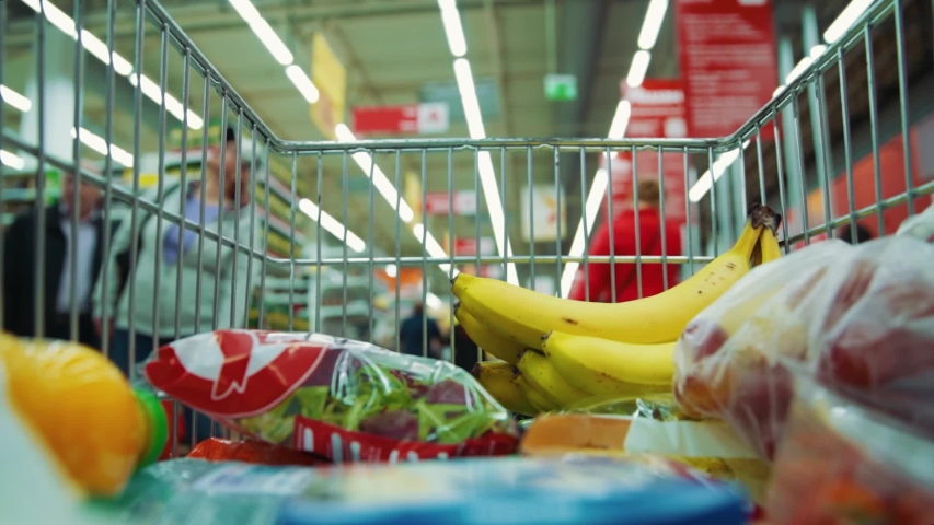 Cart with food in supermarket product lifestyle concept trade shopping trolley store buyer shopper purchase market hypermarket time lapse