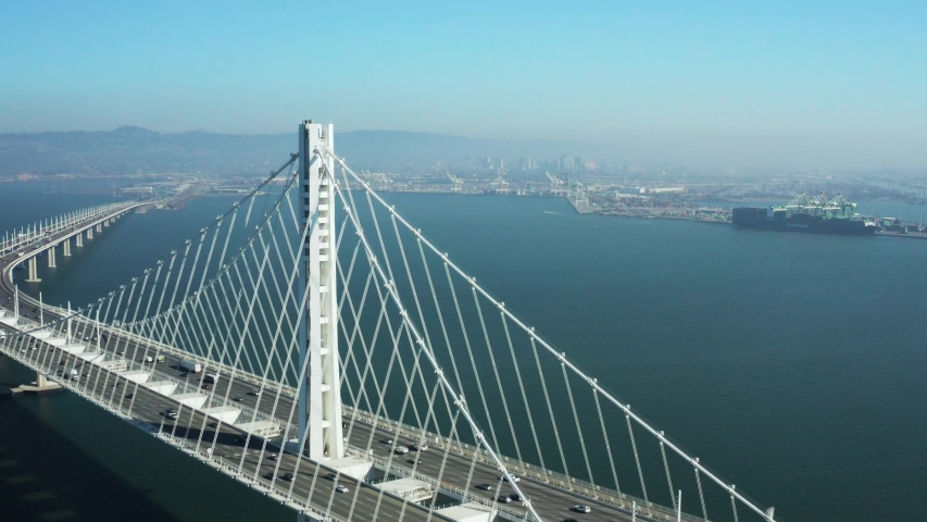 Aerial Shot of Bay Bridge pulling back with Oakland in background as cars commute, San Francisco California
