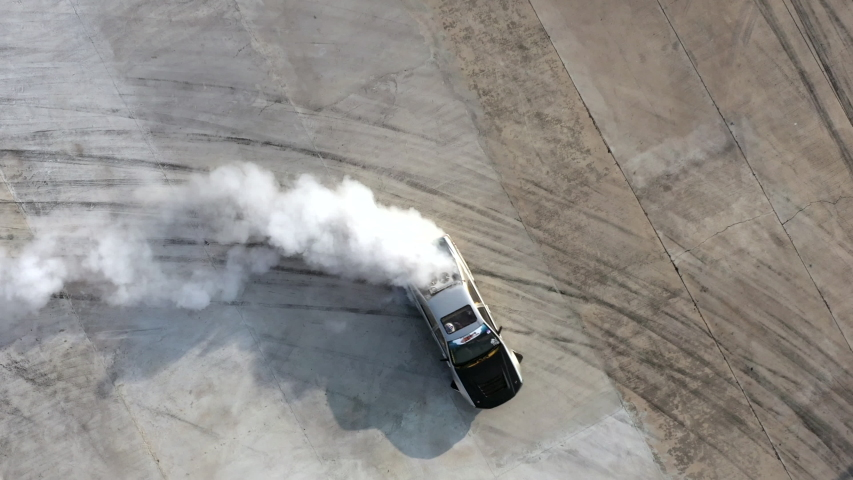 Drifting car, Aerial view professional driver drifting car on asphalt race track with black tire skid mark texture and background, Race drift car with smoke from burning tires on speed track, 4k