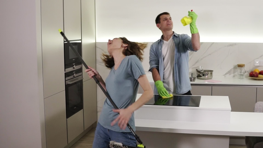 Two young people dancing together and emotionally singing using broom and cleaning tools as as microphones while cleaning in kitchen. Happy couple enjoying time, feel like rock stars Royalty-Free Stock Footage #1045712608