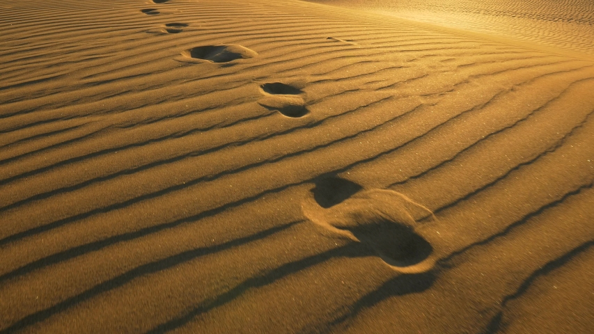 Footprints in the sand in desert at warm sunset lights. Сamera follows footprints in big sand dune. UHD, 4K