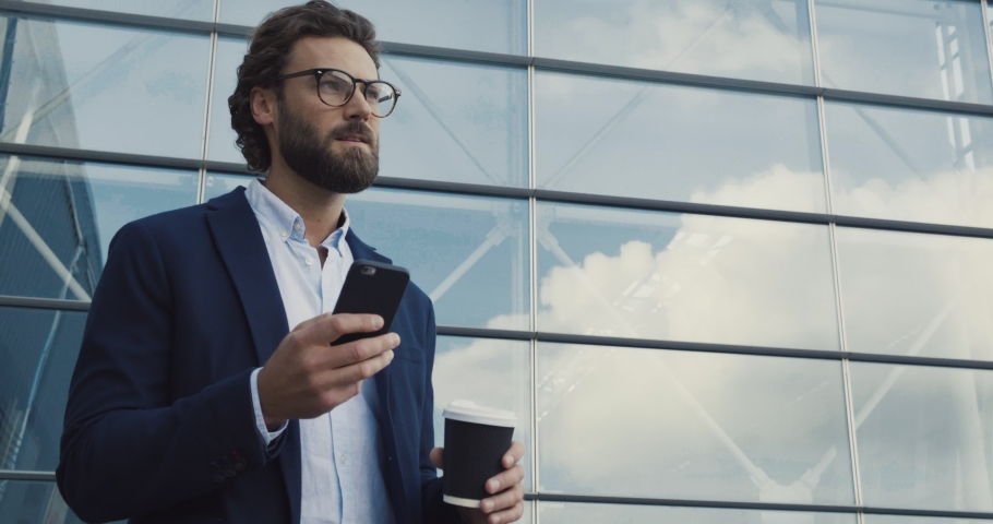 Handsome bearded Startup Businessman in Glasses using mobile Phone. Young man texting Messages, cheating on his Smartphone while walking in Office District. Business. Social Networking. People. Apps. Royalty-Free Stock Footage #1045775032