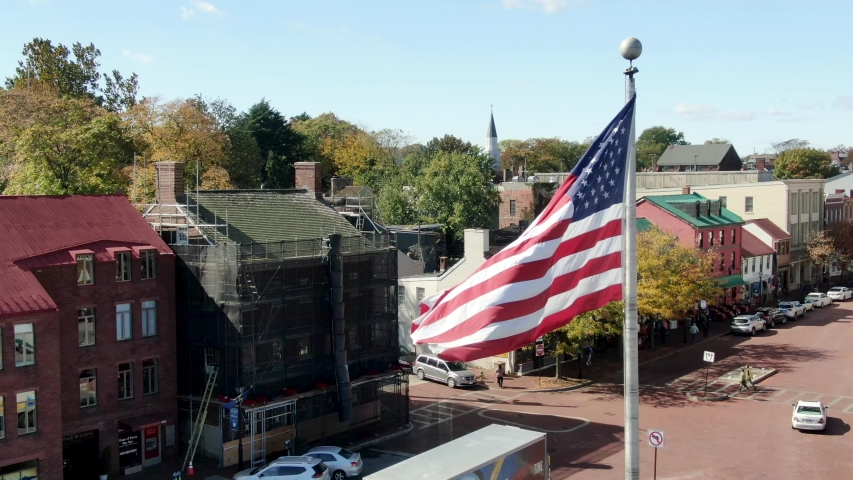 Annapolis , MD / United States - 10 23 2019: Close-up aerial of US American flag waving above Main Street and State House, establishing shot