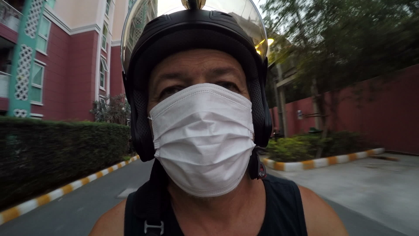 Riding a motorbike through the streets of Thailand in a gauze bandage during the Coronavirus epidemic. Faster shooting. Timelapse. Pattaya. Evening time.