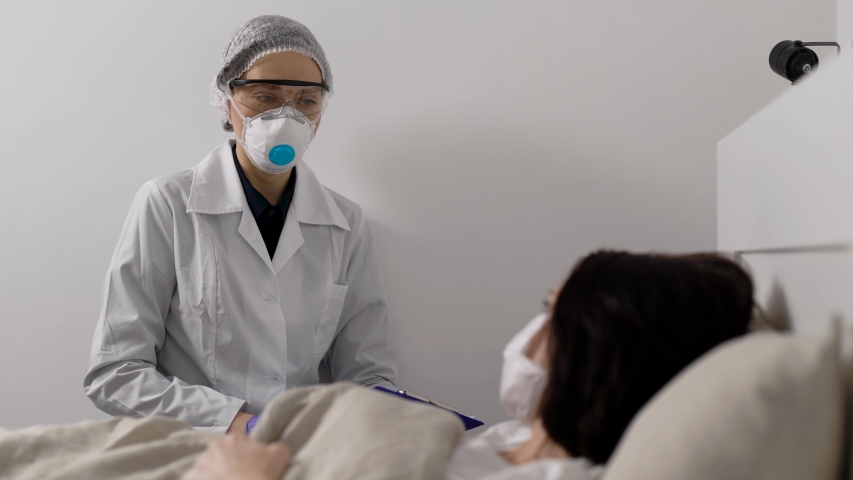 The doctor next to a seriously ill woman. Viral infection is everywhere. The patient is wearing a protective mask. Coronavirus affects the respiratory system.