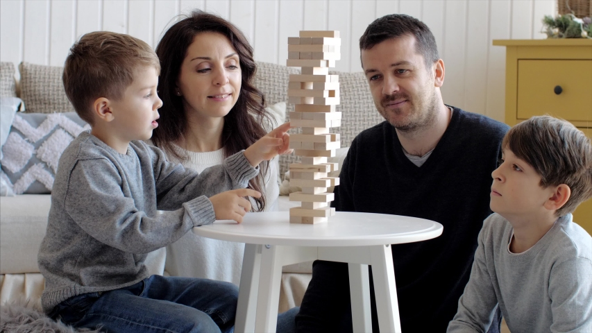 Family of four people is playing in board game with wooden tower together at home. Junior son is pulls out the brick and tower is crumbling