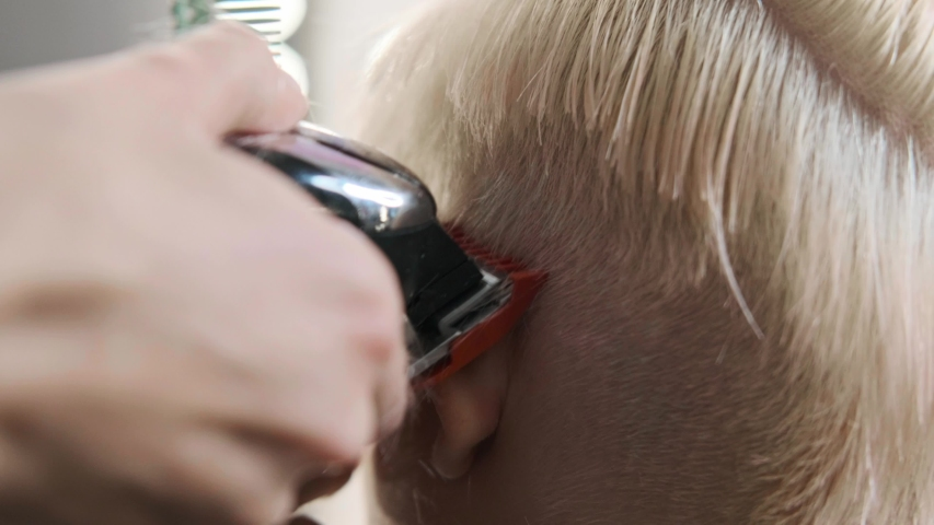 The hairdresser cuts blonde female client with a trimmer. A short pixie haircut and shaved temples . Ornament on the hair. | Shutterstock HD Video #1045816648