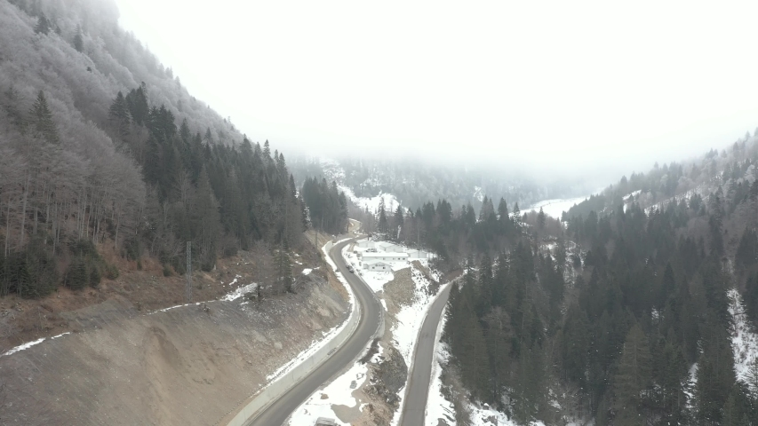 Drone rises and flies over the winter forest that covers the mountains, and narrow winding mountain roads where cars are driving. Branches of fir and pine trees are covered with snow | Shutterstock HD Video #1045838113