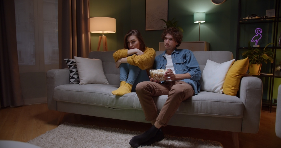 Young good looking Caucasian guy and girl watching interesting film on TV together with popcorn in the dark living room on the couch. Quarantine, pandemic, virus. Stay home | Shutterstock HD Video #1045839049