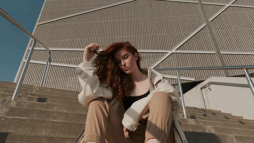 Young Red-Haired Girl On The Street. Girl Has Long Curly Hair. Urban Fashion Concept. Pretty Girl In Raincoat And Sneakers Sits On The Stairs Of Modern Building. Girl Playing With Her Hair. | Shutterstock HD Video #1045866985