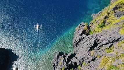 Aerial top down view of boat moving in open sea with clear and turquoise water on sunny day. Boat left the tropical lagoon. El Nido, Palawan island, Philippines